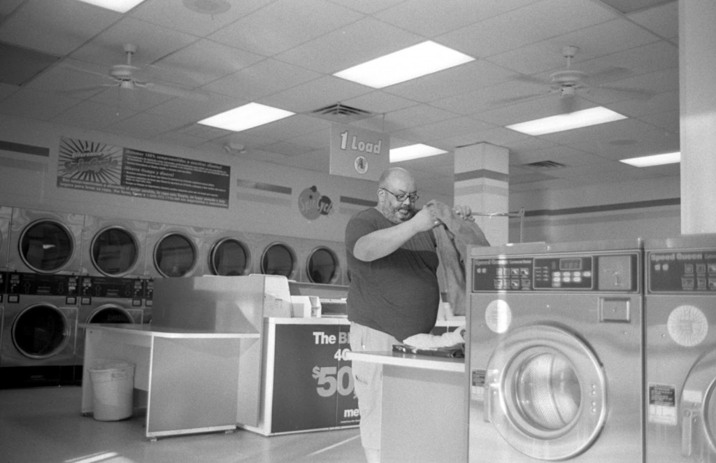 Man folds his clothes at Laundromat on the drag in Austin, Texas